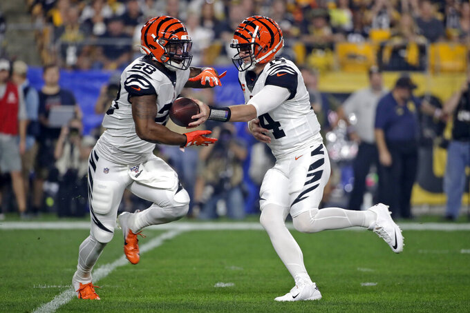 Cincinnati Bengals quarterback Andy Dalton (14) hands off to running back Joe Mixon (28) during the first half of an NFL football game against the Pittsburgh Steelers in Pittsburgh, Monday, Sept. 30, 2019. (AP Photo/Don Wright)