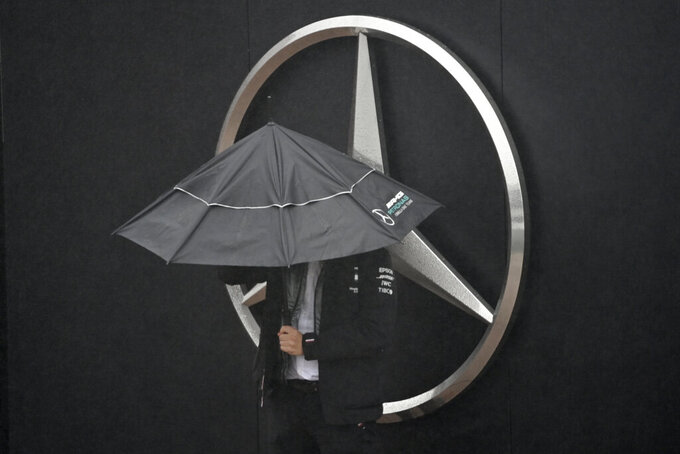 A man shelters from the rain under an umbrella next to a Mercedes logo during the second practice session for the Eifel Formula One Grand Prix at the Nuerburgring racetrack in Nuerburg, Germany, Friday, Oct. 9, 2020. The Mercedes team has found a second coronavirus case among its staff at the Eifel Grand Prix and flew in emergency replacements Friday ahead of this weekend's Formula One race. (Ina Fassbender, Pool via AP)