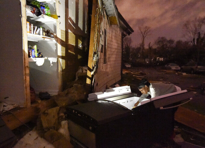 In this Tuesday, March 3, 2020 photo, Nicole (last name not given) looks through her refrigerator after it was ripped out of her home at Underwood St. and 16th Ave. N. after a tornado ripped a wall off in the Elizabeth Park neighborhood of Nashville, Tenn. (George Walker IV/The Tennessean via AP)