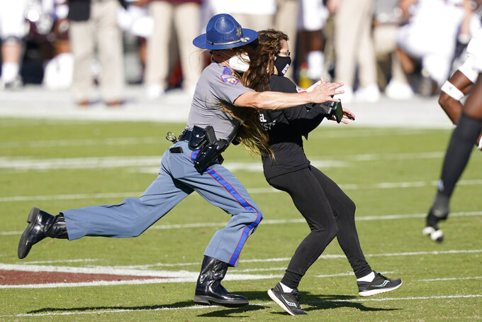 An animal rights protester is tackled by a Mississippi Highway Patrol trooper during the first half of an NCAA college football game between Texas A&M and Mississippi State in Starkville, Miss., Saturday Oct. 17, 2020. (AP Photo/Rogelio V. Solis)