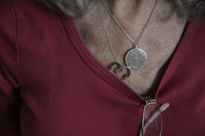 Toni Hixon, mother of Parkland school shooting victim, Chris Hixon, shows a engraved necklace with her son's face on the second anniversary of his death Friday, Feb. 14, 2020, in Hollywood, Fla. Chris Hixon, a former athletic director and military veteran, was one of 17 people killed in a school shooting on Valentine's Day two years ago at Marjory Stoneman Douglas High School. (AP Photo/Brynn Anderson)