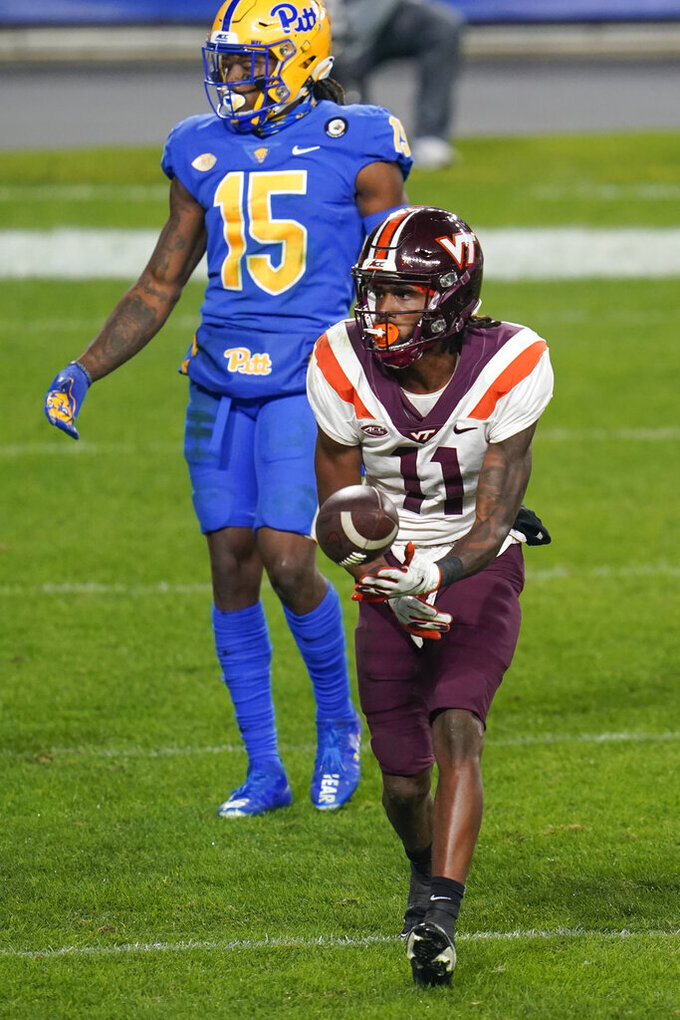 Virginia Tech wide receiver Tre Turner (11) tosses the ball to an official past Pittsburgh defensive back Jason Pinnock (15) after making his second touchdown catch during the first half of an NCAA college football game, Saturday, Nov. 21, 2020, in Pittsburgh. (AP Photo/Keith Srakocic)