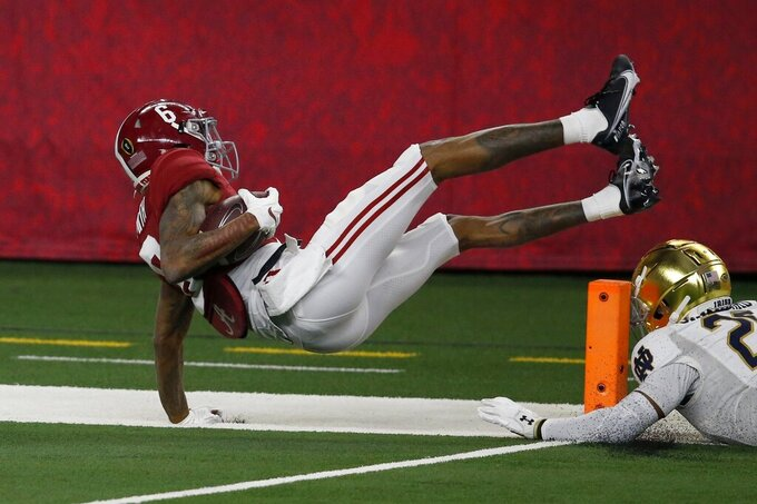Alabama wide receiver DeVonta Smith (6) leaps into the end zone or a touchdown after getting past Notre Dame safety Shaun Crawford (20) in the first half of the Rose Bowl NCAA college football game in Arlington, Texas, Friday, Jan. 1, 2021. (AP Photo/Roger Steinman)