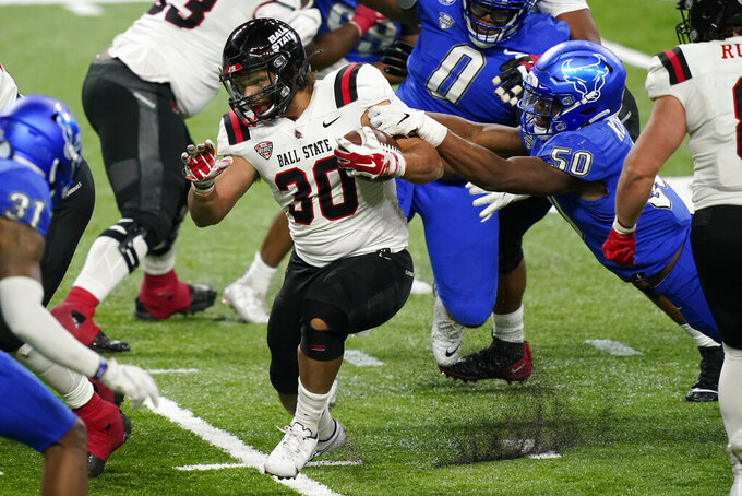 Ball State running back Tye Evans (30) rushes during the second half of the Mid-American Conference championship NCAA college football game against Buffalo, Friday, Dec. 18, 2020 in Detroit. (AP Photo/Carlos Osorio)