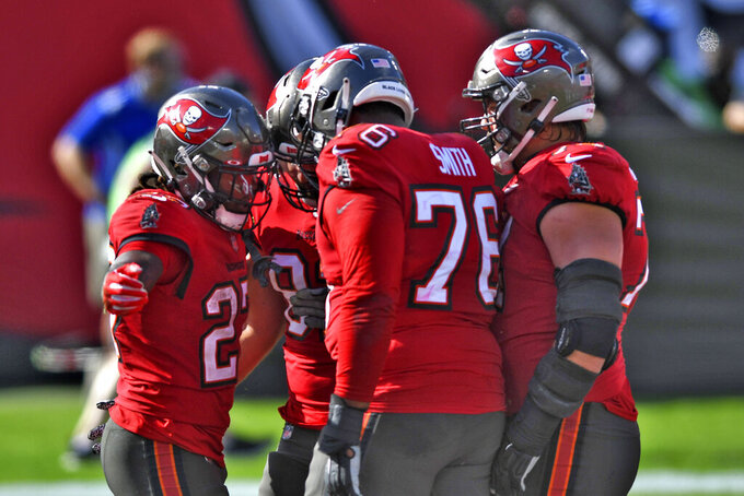 Tampa Bay Buccaneers running back Ronald Jones II (27) celebrates his score against the Minnesota Vikings with teammates, including offensive tackle Donovan Smith (76) during the first half of an NFL football game Sunday, Dec. 13, 2020, in Tampa, Fla. (AP Photo/Jason Behnken)