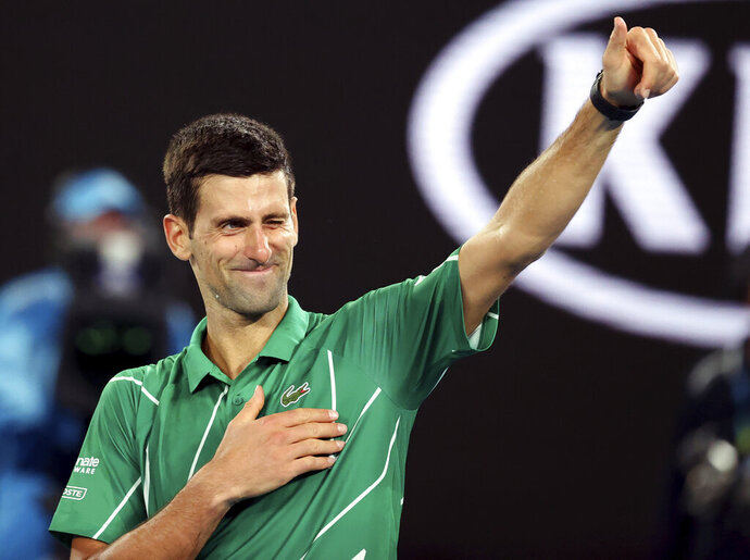 Serbia's Novak Djokovic celebrates after defeating Germany's Jan-Lennard Struff in their first round singles match the Australian Open tennis championship in Melbourne, Australia, Monday, Jan. 20, 2020. (AP Photo/Lee Jin-man)