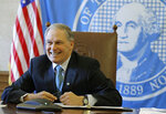 FILE - In this Wednesday, Feb. 27, 2019 file photo, Washington Gov. Jay Inslee sits in front of the state seal as he takes part in a conference call meeting with members of the AARP, at the Capitol in Olympia, Wash. Inslee's proposal for a limited public health care option cleared the state House of Representatives Friday, March 8, 2019, advancing what he has called the most practical option for expanding health coverage — and bringing to his state a national debate over what universal health care means. (AP Photo/Ted S. Warren, File)
