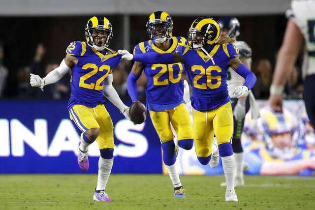 Los Angeles Rams cornerback Troy Hill, left, celebrates after his interception with Marqui Christian, right, and Jalen Ramsey during the second half of an NFL football game against the Seattle Seahawks Sunday, Dec. 8, 2019, in Los Angeles. (AP Photo/Marcio Jose Sanchez)