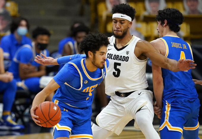 UCLA guard Johnny Juzang is defended by Colorado guard D'Shawn Schwartz during the second half of an NCAA college basketball game Saturday, Feb. 27, 2021, in Boulder, Colo. (AP Photo/David Zalubowski)