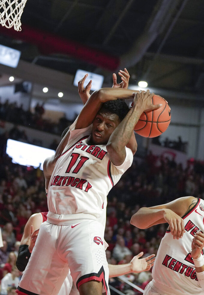 Western Kentucky guard Taveion Hollingsworth (11) and center Charles Bassey (23) pull down a defensive rebound during the second half of an NCAA college basketball game against Wisconsin, Saturday, Dec. 29, 2018, in Bowling Green, Ky. (AP Photo/Tim Broekema)