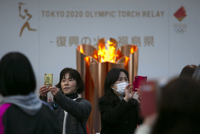 FILE - In this March 24, 2020, file photo, people take pictures with the Olympic Flame during a ceremony in Fukushima City, Japan. The Olympic flame has been removed from public display in Japan, and it's not clear when it will reappear again or where. The flame arrived in Japan from Greece on March 26. (AP Photo/Jae C. Hong, File)