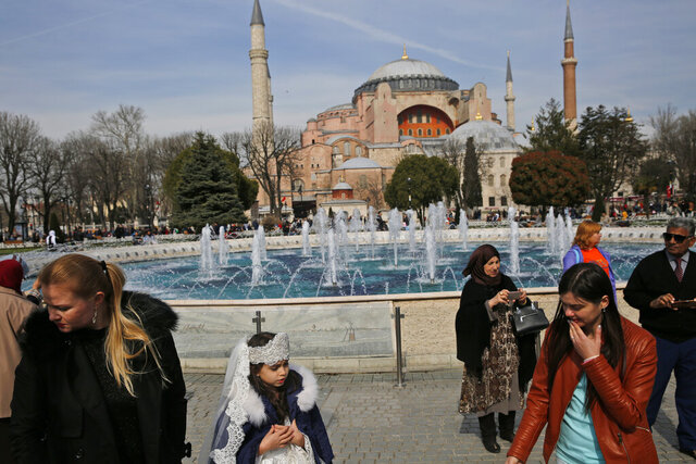 FILE - In this Friday, March 24, 2017 file photo, people walk backdropped by the Byzantine-era Hagia Sophia, one of Istanbul's main tourist attractions, in the historic Sultanahmet district of Istanbul. The 6th-century building is now at the center of a heated debate between conservative groups who want it to be reconverted into a mosque and those who believe the World Heritage site should remain a museum. (AP Photo/Lefteris Pitarakis, File)