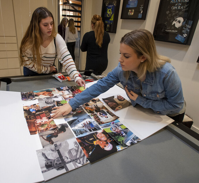 Classmates Faith Robinson, left, and Chloe Stephens, right, place photos of Walker Vincent on a board during a 16th birthday party for Walker at Leslie Jacob's home on Sunday, December 29, 2019 in Lafayette, La. Walker Vincent was one of the victims in the plane crash on Saturday. Family and friends threw him a birthday party where they released LSU balloons and marked gifts with their favorite memories of Walker for his father.  (Brad Kemp/The Advocate via AP)