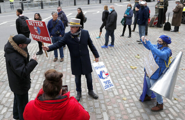 Pro EU supporters argue with Brexit supporters in London, Wednesday, Nov. 11, 2020. Negotiations continue on London between the EU bloc and British officials to agree A Brexit deal as Britain is due to split from Europe  from January 1. (AP Photo/Frank Augstein)