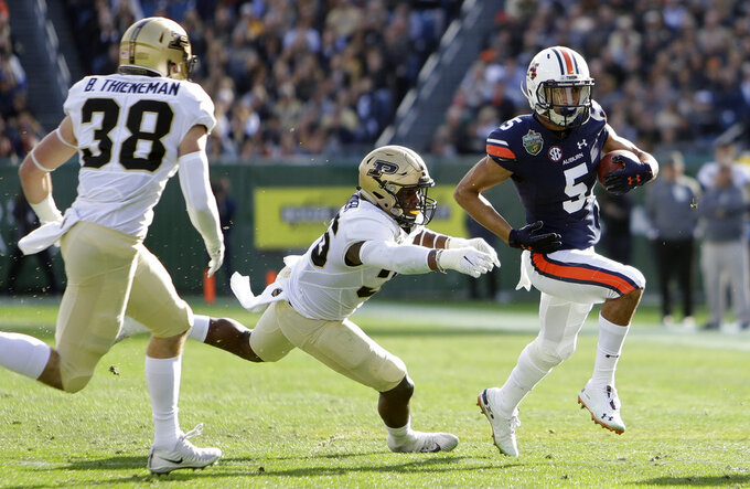 Auburn wide receiver Anthony Schwartz, right, runs past Purdue defenders Brennan Thieneman, left, and Jaylan Alexander, center, in the first half of the Music City Bowl NCAA college football game Friday, Dec. 28, 2018, in Nashville, Tenn. (AP Photo/Mark Humphrey)