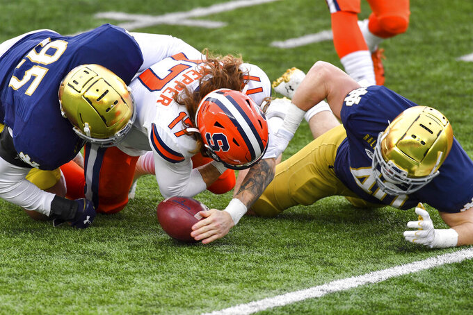 Notre Dame defensive lineman Myron Tagovailoa-Amosa (95) and linebacker Drew White (40) sack Syracuse quarterback Rex Culpepper (17) causing a fumble in the first half of an NCAA college football game Saturday, Dec. 5, 2020, in South Bend, Ind. (Matt Cashore/Pool Photo via AP)