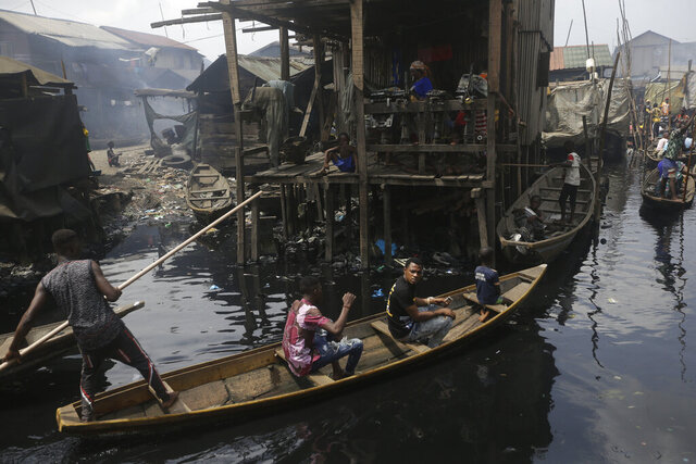 FILE - In this Saturday, March 21, 2020 file photo, people travel by canoe during a coronavirus lockdown in the floating slum of Makoko in Lagos, Nigeria. Up to 150 million people could slip into extreme poverty, living on less than $1.90 a day, by late next year depending on how badly economies shrink during the COVID-19 pandemic, the World Bank said Wednesday, Oct. 7, 2020 in an outlook grimmer than before. (AP Photo/Sunday Alamba, File)