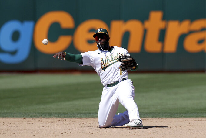 Oakland Athletics' Elvis Andrus (17) throws out Texas Rangers' Nathaniel Lowe from his knees in the sixth inning of a baseball game Saturday, Sept. 11, 2021, in Oakland. (AP Photo/Scot Tucker)