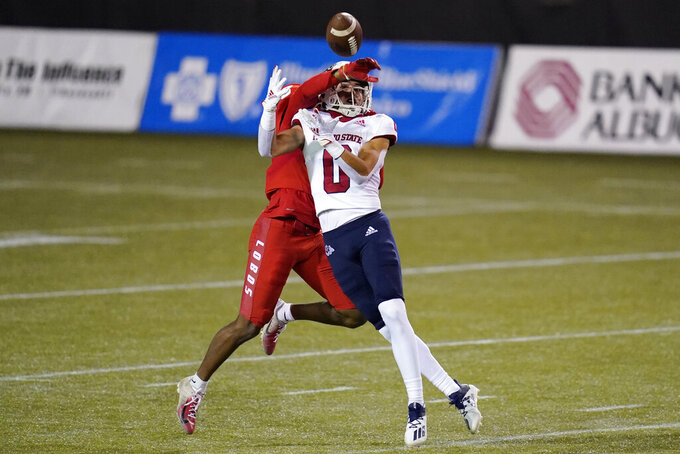 Fresno State wide receiver Mac Dalena (0) makes a catch over New Mexico cornerback Donte Martin during the first half of an NCAA college football game Saturday, Dec. 12, 2020, in Las Vegas. (AP Photo/John Locher)
