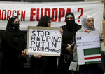 Chechen protesters hold a banner that reads: