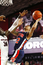 Auburn guard J'Von McCormick (12) shoots while being defended by Georgia forward Derek Ogbeide (34) during an NCAA college basketball game Wednesday, Feb. 27, 2019, in Athens, Ga. (Joshua L. Jones/Athens Banner-Herald via AP)