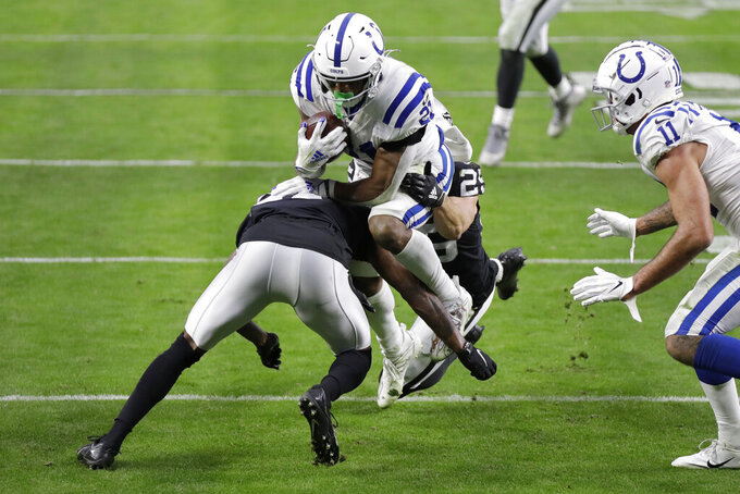 Las Vegas Raiders cornerback Trayvon Mullen, left, tackles Indianapolis Colts running back Nyheim Hines (21) during the first half of an NFL football game, Sunday, Dec. 13, 2020, in Las Vegas. (AP Photo/Isaac Brekken)