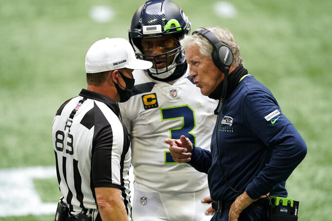 Seattle Seahawks quarterback Russell Wilson (3) and Seattle Seahawks head coach Pete Carroll speak to back judge Shawn  Hochuli (83) during the first half of an NFL football game against the Atlanta Falcons, Sunday, Sept. 13, 2020, in Atlanta. (AP Photo/John Bazemore)