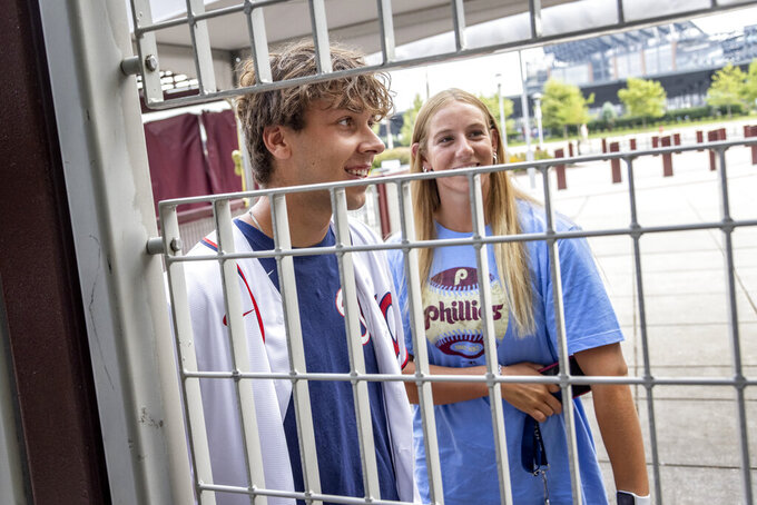 Fans stand at the locked gate of Citizens Bank Park after the baseball game between the Philadelphia Phillies and Washington Nationals was postponed due to COVID-19 issues among the Nationals, Wednesday, July 28, 2021, in Philadelphia. (AP Photo/Laurence Kesterson)