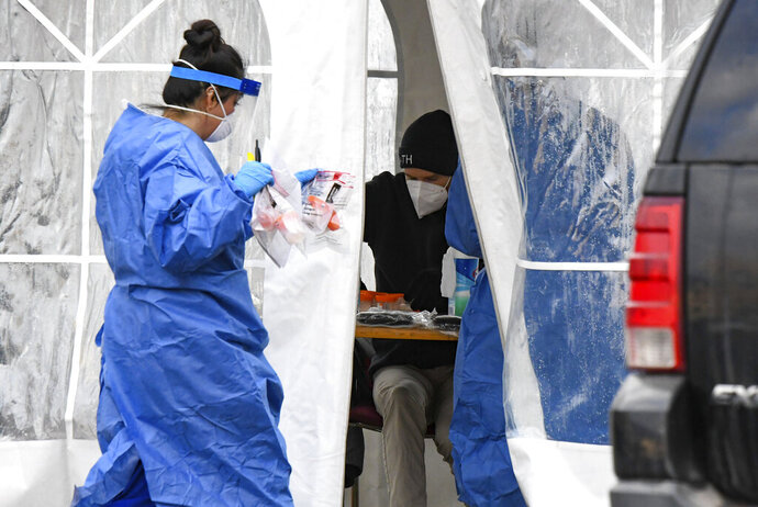A nurse walks COVID-19 tests back to the tent at the free COVID-19 testing site on Monday, Nov. 23, 2020 in Glenwood Springs, Colo. (Chelsea Self/Glenwood Springs Post Independent via AP)