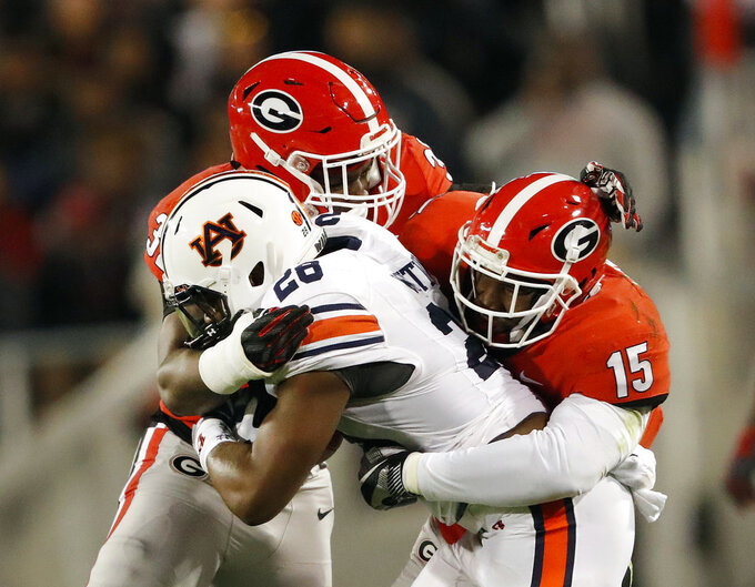 Auburn running back JaTarvious Whitlow (28) is brought down by Georgia linebackers Monty Rice (32) and D'Andre Walker (15) during the first half of an NCAA college football game Saturday, Nov. 10, 2018, in Athens, Ga. (AP Photo/John Bazemore)