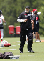 Atlanta Falcons head coach Dan Quinn jogs across the field during an NFL football practice Tuesday, June 11, 2019, in Flowery Branch, Ga. (AP Photo/John Bazemore)