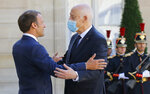 French President Emmanuel Macron, left, welcomes Tunisian President Kais Saied who wears a protective mask for bilateral talks at the Elysee Palace in Paris, Monday, June 22, 2020. Tunisian President Kais Saied is for a two-day visit in France. (AP Photo/Michel Euler)