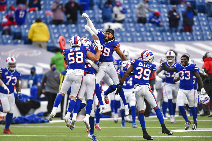 Buffalo Bills' Matt Milano (58) and Josh Norman (29) and teammates celebrate after an NFL wild-card playoff football game against the Indianapolis Colts Saturday, Jan. 9, 2021, in Orchard Park, N.Y. The Bills won the game 27-24. (AP Photo/Adrian Kraus)
