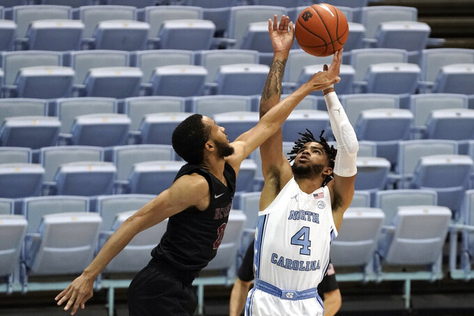 North Carolina Central guard Nicolas Fennell guards North Carolina guard R.J. Davis (4) during the first half of an NCAA college basketball game in Chapel Hill, N.C., Saturday, Dec. 12, 2020. (AP Photo/Gerry Broome)