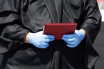 Principal Vance Fishback holds a diploma to presnt to graduates of the class of 2020 from Cabarrus Early College of Technology at the Charlotte Motor Speedway during a graduation event in Concord, N.C., Friday, June 12, 2020. Due to the coronavirus pandemic Cabarrus County schools participated in a first-of-its-kind commencement ceremony for students and family. (AP Photo/Gerry Broome)