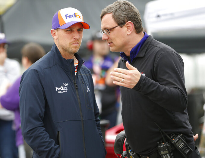 CORRECTS CREW CHIEF TO CHRIS GABEHART, INTEAD OF JIM UTTER - Denny Hamlin, left, listens to crew chief Chris Gabehart prior to qualifying for Saturday's NASCAR Cup auto race at Richmond International Raceway in Richmond, Va., Friday, April 12, 2019. (AP Photo/Steve Helber)
