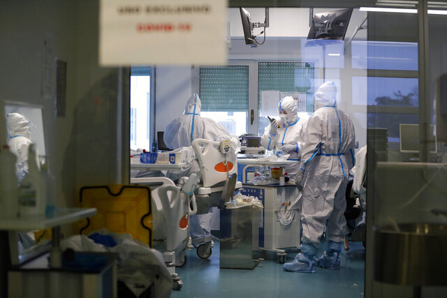 Medical personnel work inside a COVID-19 Intensive Care Unit at the military hospital in Lisbon, Wednesday, Jan. 27, 2021. The military hospital is expanding it's number of beds available to take COVID-19 patients from the National Health Service. Portugal is reporting new daily records of COVID-19 deaths and hospitalizations as a recent pandemic surge continues unabated. (AP Photo/Armando Franca)