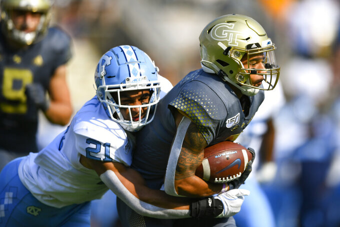Georgia Tech's Tobias Oliver (8) runs with the ball as North Carolina linebacker Chazz Surratt (21) tackles during the first half of an NCAA college football game Saturday, Oct. 5, 2019, in Atlanta. (John Amis/Atlanta Journal-Constitution via AP)