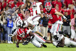 Georgia running back Zamir White (3) is tackled by South Carolina defensive back R.J. Roderick (10) and defensive back Jaylan Foster (12) during the first half of an NCAA college football game Saturday, Sept. 18, 2021, in Athens, Ga. (AP Photo/Butch Dill)