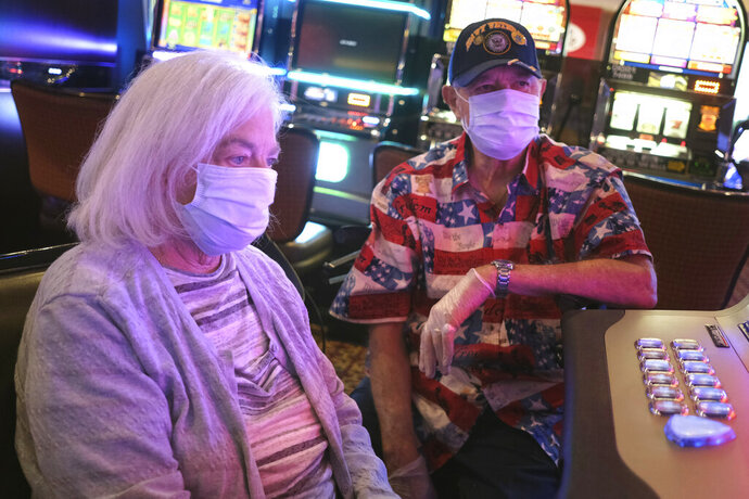 Marita and Joe Dinnini wear masks and gloves while playing a slot machine at the Golden Nugget Casino in Atlantic City, N.J., Thursday, July 2, 2020. Eager to hit the slot machines and table games after a 108-day absence, gamblers wore face masks and did without smoking and drinking Thursday as Atlantic City's casinos reopened amid the coronavirus pandemic that has drastically changed things both inside and outside the casino walls. (AP Photo/Seth Wenig)
