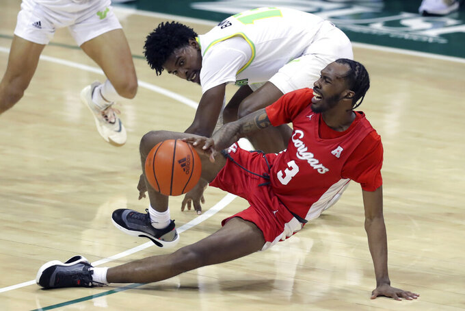 Houston's DeJon Jarreau (3) stumbles past South Florida's Justin Brown during the second half of an NCAA college basketball game Wednesday, Feb. 10, 2021, in Tampa, Fla. Houston won 82-65. (AP Photo/Mike Carlson)