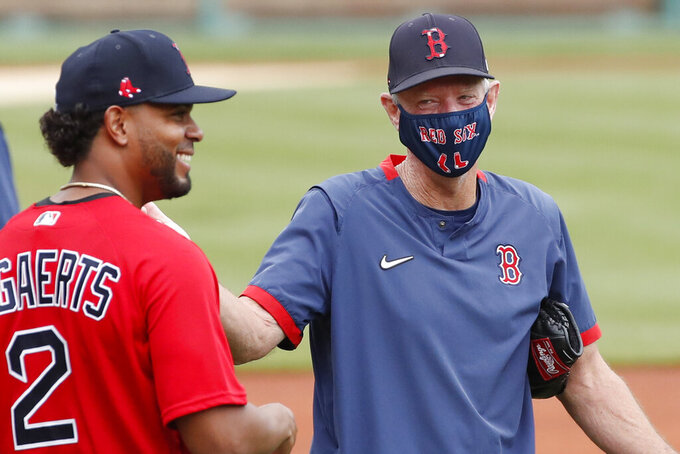 Boston Red Sox's Xander Bogaerts laughs with interim manager Ron Roenicke, right, during baseball training camp at Fenway Park, Monday, July 6, 2020, in Boston. (AP Photo/Elise Amendola)