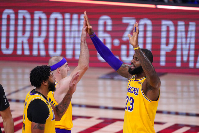 Los Angeles Lakers' LeBron James (23) celebrates with Anthony Davis, left, and Alex Caruso after an NBA conference semifinal playoff basketball game against the Houston Rockets Thursday, Sept. 10, 2020, in Lake Buena Vista, Fla. The Lakers won 110-100. (AP Photo/Mark J. Terrill)
