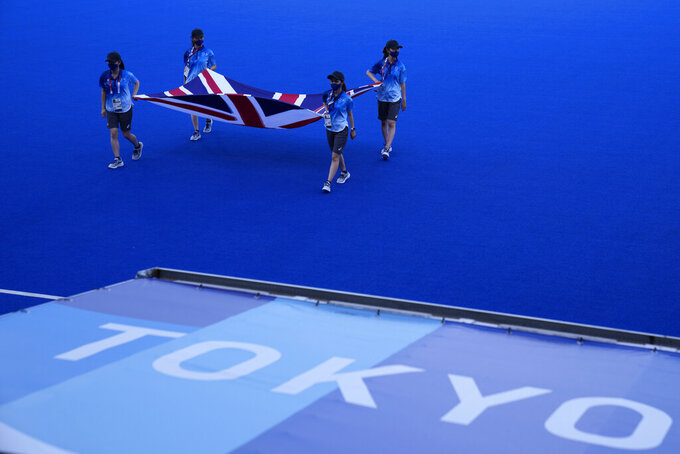 People rehearse carrying the flag of Great Britain during a break in field hockey matches at the 2020 Summer Olympics, Saturday, July 24, 2021, in Tokyo, Japan. (AP Photo/John Locher)