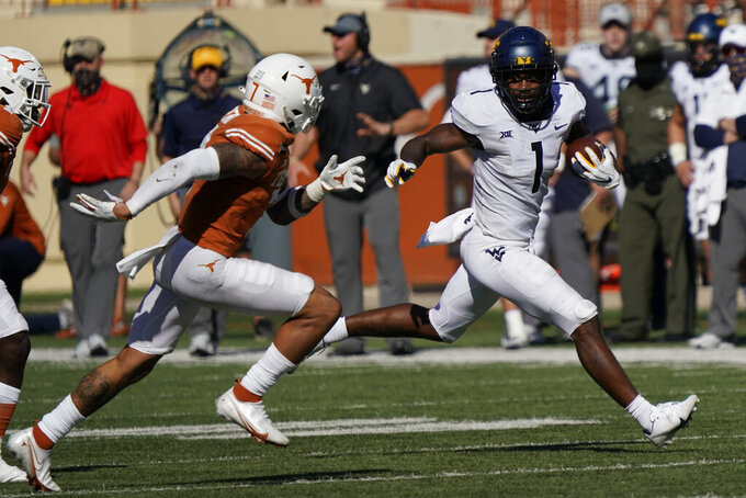 West Virginia's T.J. Simmons (1) runs after a catch as Texas' Caden Sterns (7) pursues during the second half of an NCAA college football game in Austin, Texas, Saturday, Nov. 7, 2020. (AP Photo/Chuck Burton)