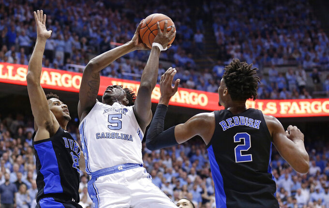 North Carolina's Nassir Little (5) drives to the basket as Duke's Cam Reddish (2) and Javin DeLaurier, left, defend during the first half of an NCAA college basketball game in Chapel Hill, N.C., Saturday, March 9, 2019. (AP Photo/Gerry Broome)