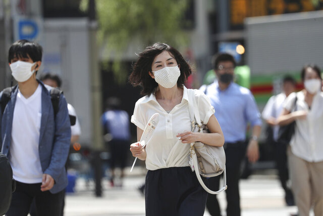 People wearing face masks to help protect against the spread of the new coronavirus pass on a crosswalk on a street in Tokyo, Tuesday, Aug, 4, 2020. (AP Photo/Koji Sasahara)