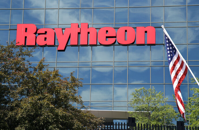 FILE - In this June 10, 2019, file photo, an American flag flies in front of the facade of Raytheon's Integrated Defense Systems facility, in Woburn, Mass. China's government said Monday, Oct. 26, 2020, it will impose sanctions on U.S. military contractors including Boeing Co.'s defense unit and Lockheed Martin Corp. for supplying weapons to rival Taiwan, stepping up a feud with Washington over security and Beijing's strategic ambitions. (AP Photo/Elise Amendola, File)