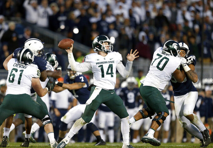 FILE - In this Oct. 13, 2018, file photo, Michigan State quarterback Brian Lewerke (14) throws a pass against Penn State during the second half of an NCAA college football game in State College, Pa. Whether the priority is secrecy or modesty, Michigan State has said little about any changes on the offensive side of the ball, but once the games start, there will be nowhere to hide. The Spartans are under pressure--from their own fans, first and foremost--to produce. (AP Photo/Chris Knight, File)