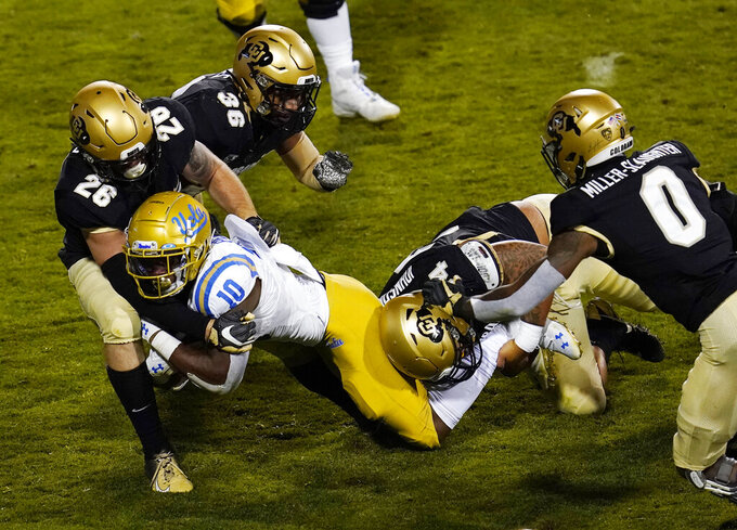 UCLA running back Demetric Felton, front center, is stopped by, from left to right, Colorado linebacker Carson Wells, linebacker Akil Jones, defensive end Mustafa Johnson and cornerback Chris Miller in the first half of an NCAA college football game Saturday, Nov. 7, 2020, in Boulder, Colo. (AP Photo/David Zalubowski)